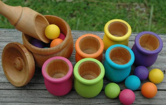 Contenants et boules en bois peint, pour classer les couleurs et pratiquer la dextérité avec la cuiller.